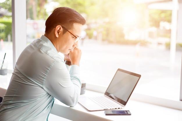 Homem de negócios de ásia trabalhando com laptop enquanto está sentado a loja de café