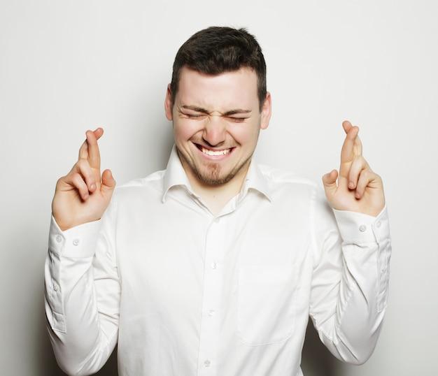 Homem de negócios de camisa, mantendo os dedos cruzados