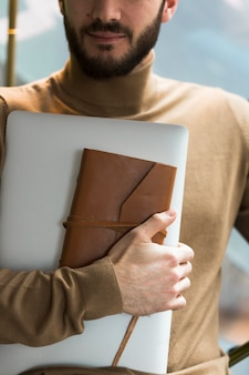 Homem de negócios de close-up com laptop e agenda