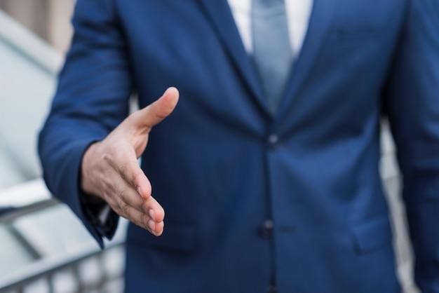 Homem de negócios de close-up preparado para apertar a mão