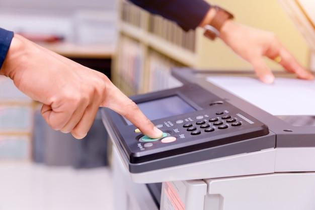 Homem de negócios de close-up pressione o botão de mão no painel da impressora.