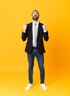Homem de negócios de comprimento total sobre parede amarela isolada surpreso e apontando para cima