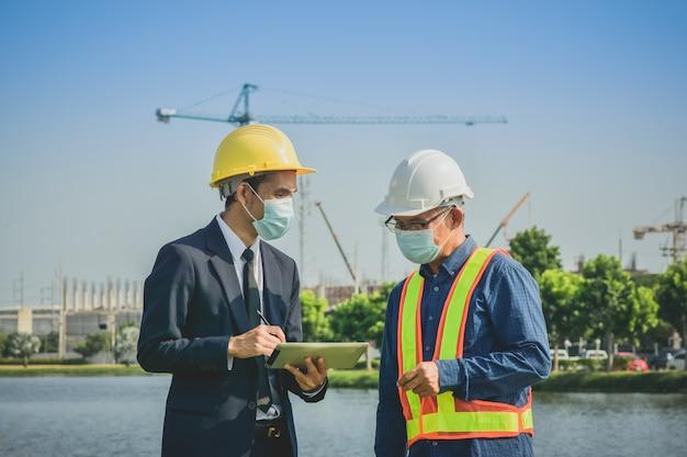 Homem de negócios de duas pessoas falando com sênior na construção do local sobre projeto de planta imobiliária e projeto empresarial