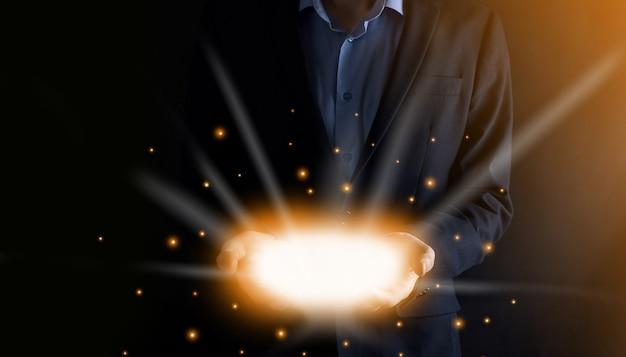 Homem de negócios de mãos abertas com luzes brilhantes em fundo escuro.