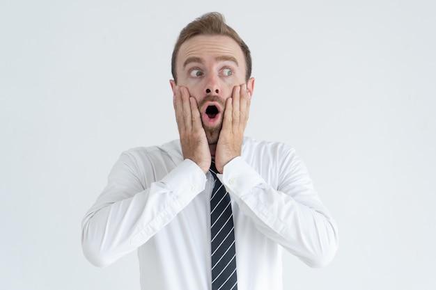 Homem de negócios de meia-idade chocado tocando as bochechas e desviar o olhar com a boca aberta