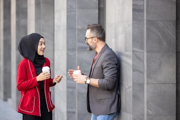 Homem de negócios de meia idade com barba bonita tomando café em uma cafeteria ao ar livre com uma jovem e bela mulher muçulmana