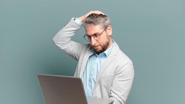 Homem de negócios de meia-idade com um laptop