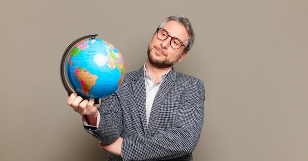 Homem de negócios de meia-idade com um mapa do globo terrestre