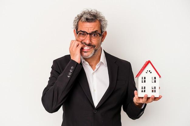 Homem de negócios de meia idade segurando contas e modelo de casa isolado em fundo azul, roendo as unhas, nervoso e muito ansioso.