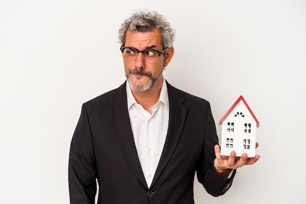 Homem de negócios de meia-idade segurando contas e modelo de casa isolado em um fundo azul confuso, sente-se em dúvida e inseguro.