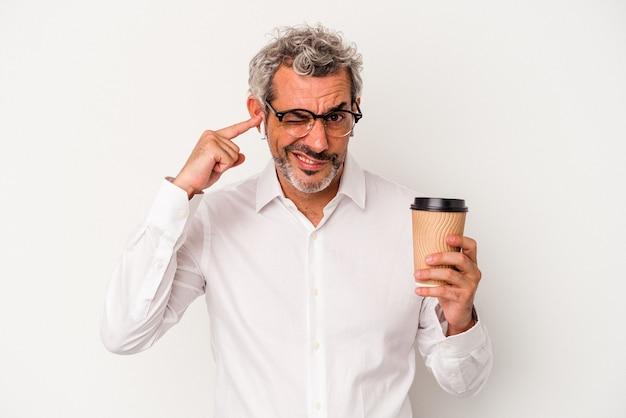 Homem de negócios de meia idade segurando um café para levar isolado no fundo branco, cobrindo as orelhas com as mãos.