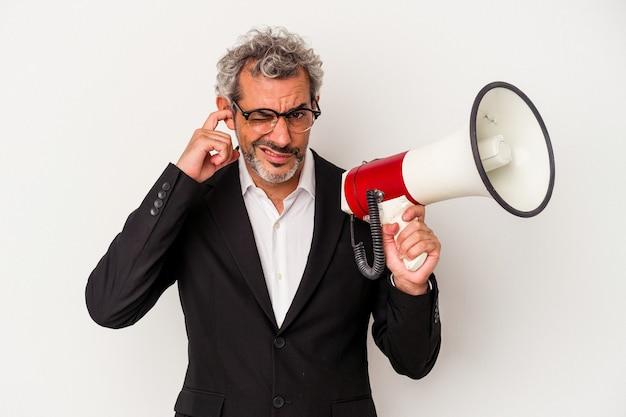 Homem de negócios de meia-idade segurando um megafone isolado no fundo branco, cobrindo as orelhas com as mãos.