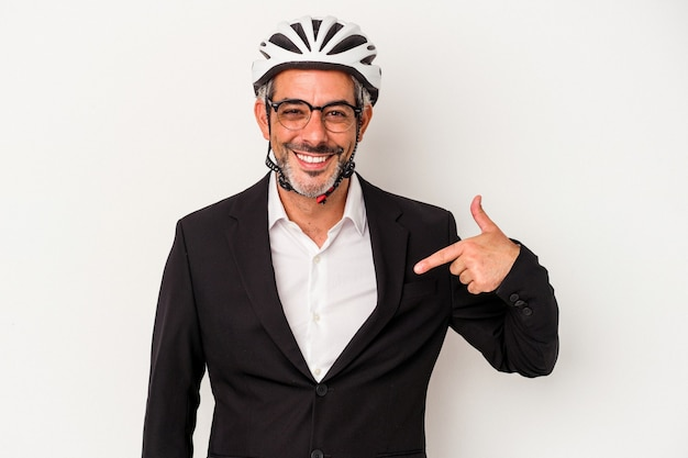 Homem de negócios de meia-idade usando um capacete de bicicleta isolado em um fundo azul pessoa apontando com a mão para um espaço de cópia de camisa, orgulhoso e confiante