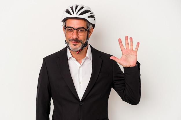 Homem de negócios de meia-idade usando um capacete de bicicleta isolado no fundo azul, sorrindo alegre mostrando o número cinco com os dedos.