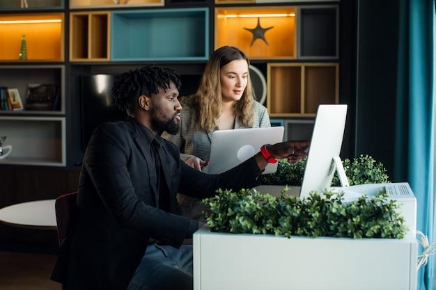 Homem de negócios de pele escura em um terno escuro trabalha em um computador em um escritório moderno