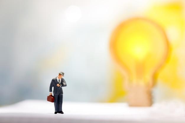 Homem de negócios de pessoas em miniatura, olhando para o relógio com a idéia da lâmpada
