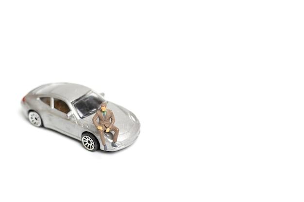 Homem de negócios de pessoas em miniatura sentado em um carro e copia o espaço para texto