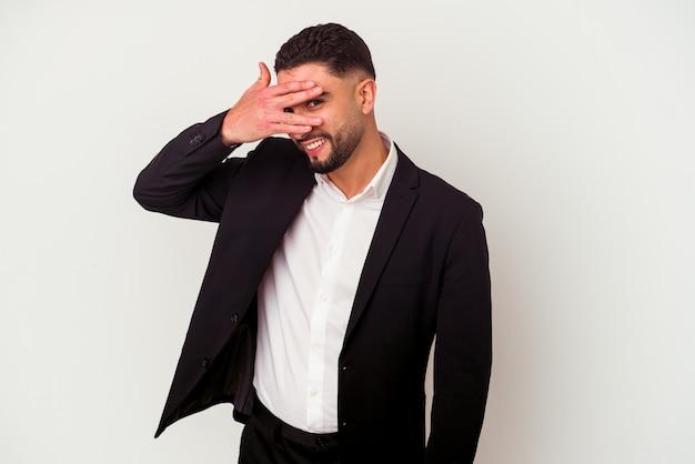 Homem de negócios de raça mista jovem isolado na parede branca piscar para a câmera por entre os dedos, rosto cobrindo vergonha.