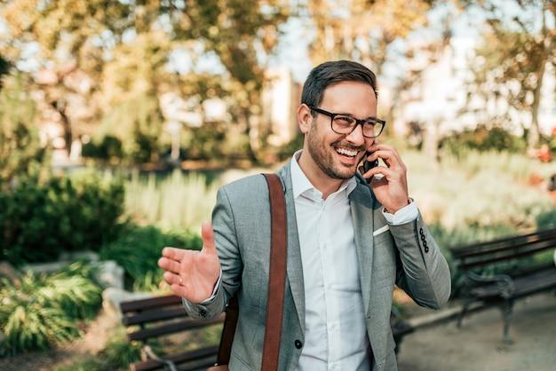 Homem de negócios de sorriso que fala no telefone esperto no parque.