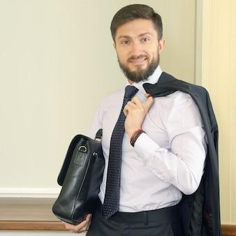 Homem de negócios de sucesso com uma pasta e um terno nas mãos