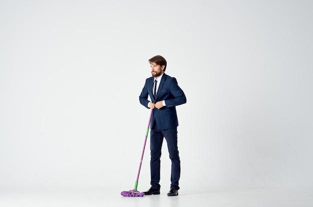 Homem de negócios de terno com um esfregão nas mãos prestando serviços de limpeza de pisos