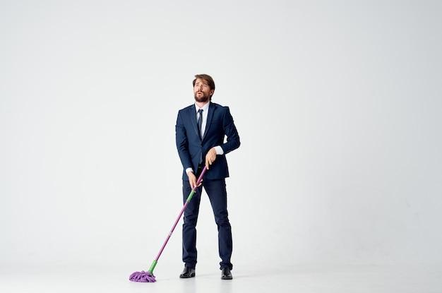 Homem de negócios de terno com um esfregão no serviço de limpeza de mãos