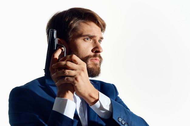 Homem de negócios de terno com uma arma nas mãos detetive cautela crime.