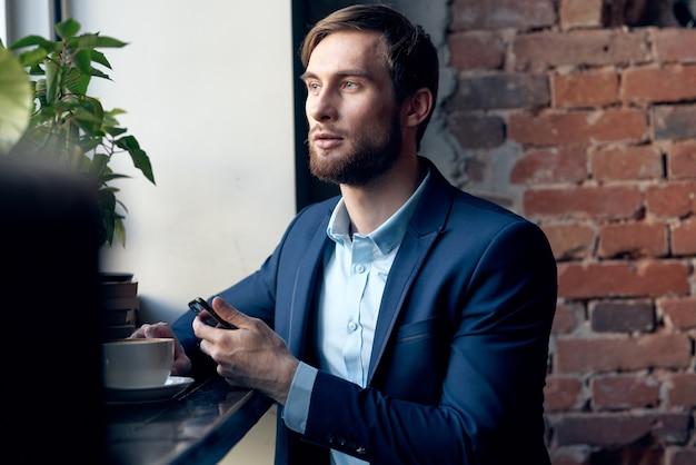 Homem de negócios de terno de funcionário de um café falando ao telefone