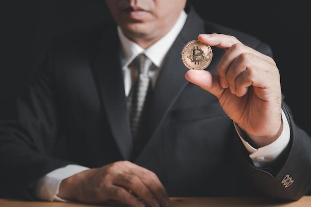 Homem de negócios de terno e gravata segurando uma moeda
