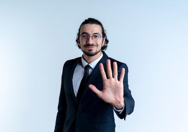 Homem de negócios de terno preto e óculos aparecendo e apontando para cima com os dedos número cinco sorrindo em pé sobre uma parede branca