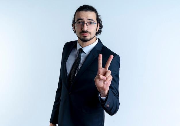 Homem de negócios de terno preto e óculos aparecendo e apontando para cima com os dedos número dois olhando com uma cara séria em pé sobre uma parede branca