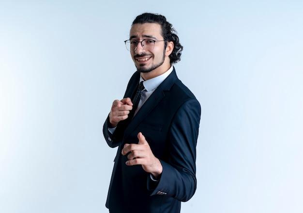 Homem de negócios de terno preto e óculos apontando com o dedo indicador para a frente sorrindo alegremente em pé sobre uma parede branca