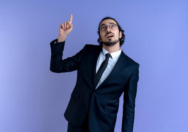 Homem de negócios de terno preto e óculos apontando com o dedo indicador para cima olhando para cima em pé sobre a parede azul