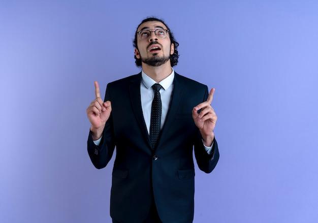 Homem de negócios de terno preto e óculos apontando com o dedo indicador para cima parecendo confiante em pé sobre a parede azul