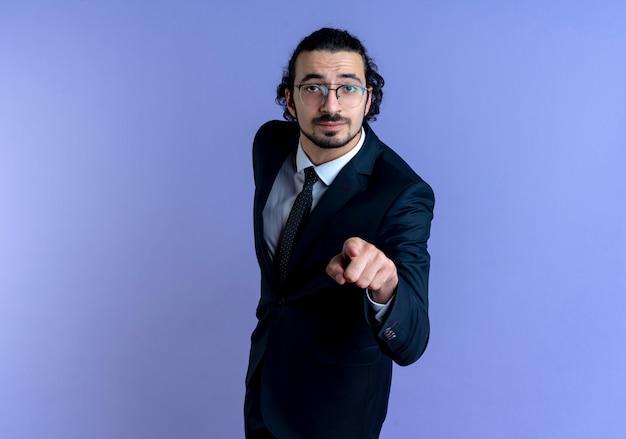 Homem de negócios de terno preto e óculos apontando com o dedo para a frente parecendo confiante em pé sobre a parede azul
