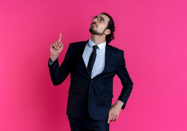 Homem de negócios de terno preto e óculos apontando com o dedo para cima parecendo confuso em pé sobre a parede rosa