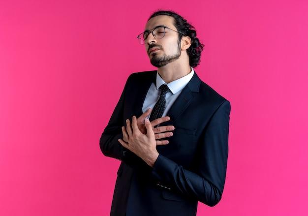 Homem de negócios de terno preto e óculos com as mãos cruzadas sobre o peito olhando para o lado e sentindo-se grato em pé sobre a parede rosa
