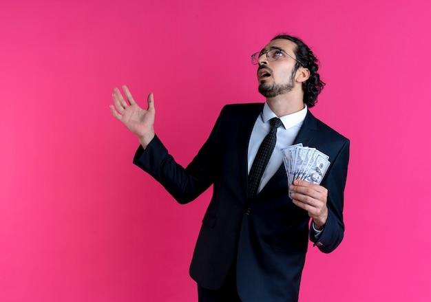 Homem de negócios de terno preto e óculos mostrando dinheiro, olhando para cima confuso com o braço estendido em pé sobre a parede rosa