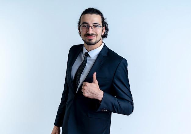 Homem de negócios de terno preto e óculos olhando para a frente com uma expressão confiante sorrindo mostrando os polegares em pé sobre uma parede branca