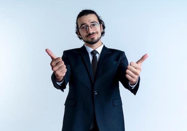 Homem de negócios de terno preto e óculos olhando para a frente sorrindo alegremente mostrando os polegares em pé sobre uma parede branca
