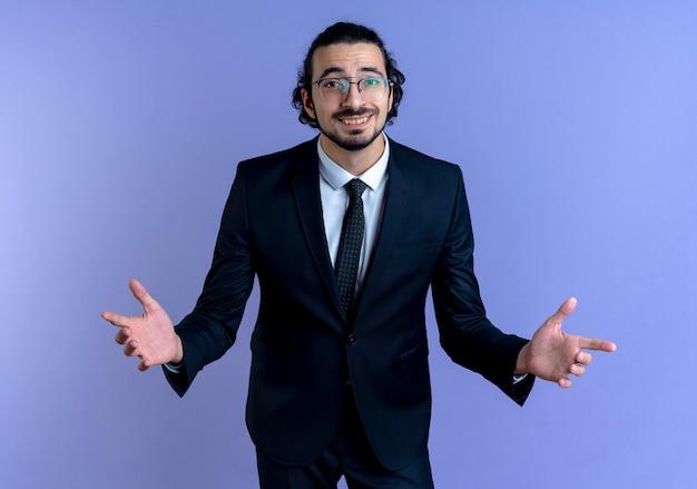 Homem de negócios de terno preto e óculos olhando para a frente sorrindo e fazendo um gesto de boas-vindas com as mãos em pé sobre a parede azul