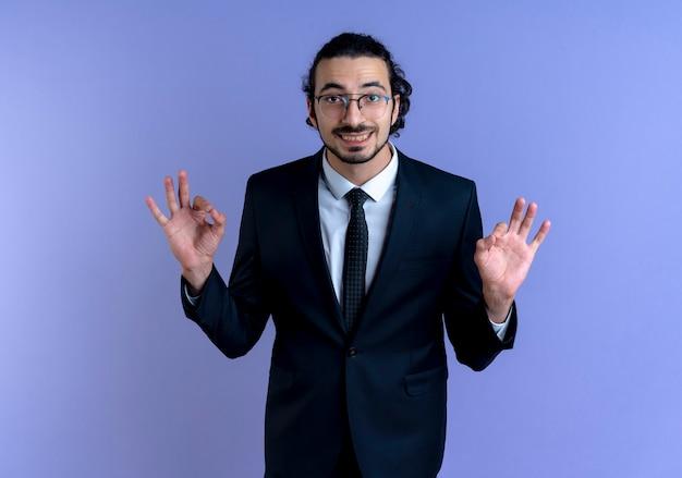 Homem de negócios de terno preto e óculos olhando para a frente sorrindo, fazendo um gesto de meditação com os dedos em pé sobre a parede azul