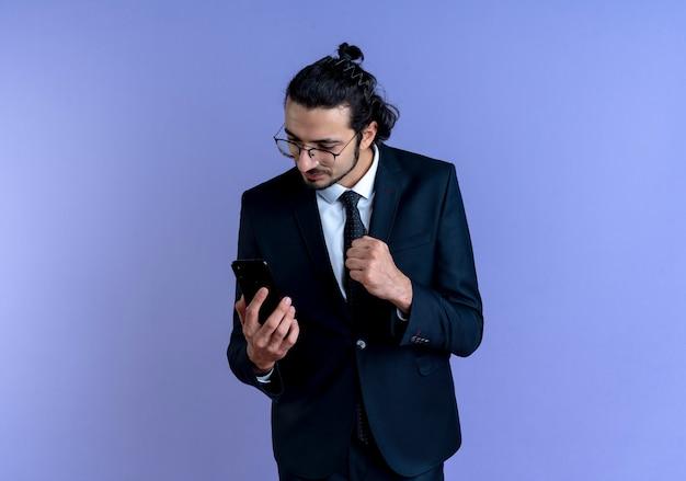 Homem de negócios de terno preto e óculos olhando para a tela de seu smartphone cerrando o punho feliz e positivo em pé sobre a parede azul