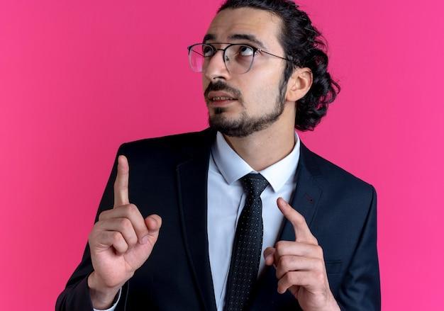 Homem de negócios de terno preto e óculos olhando para cima apontando com os dedos para o lado em pé sobre a parede rosa