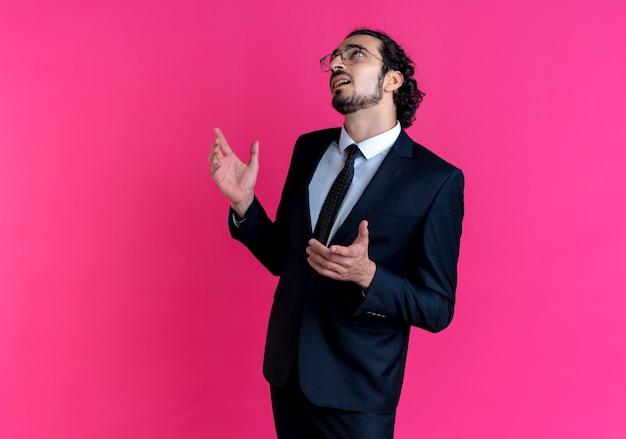 Homem de negócios de terno preto e óculos olhando para cima com a mão levantada confuso em pé sobre a parede rosa