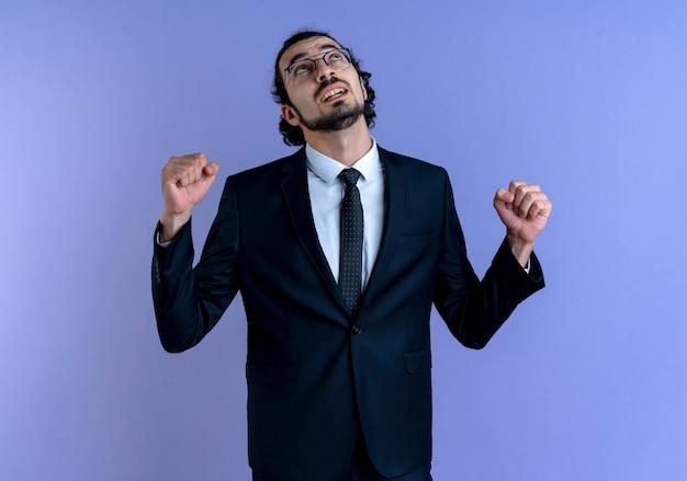Homem de negócios de terno preto e óculos olhando para cima com o punho cerrado