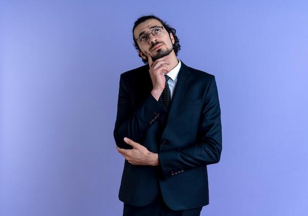 Homem de negócios de terno preto e óculos olhando para cima com uma expressão pensativa no rosto em pé sobre a parede azul