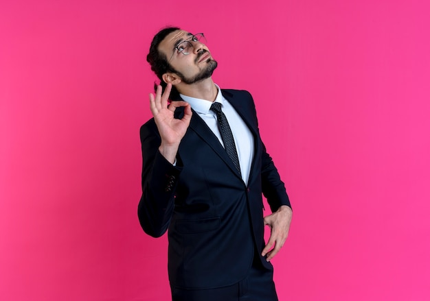 Homem de negócios de terno preto e óculos olhando para cima mostrando uma placa de ok em pé sobre a parede rosa