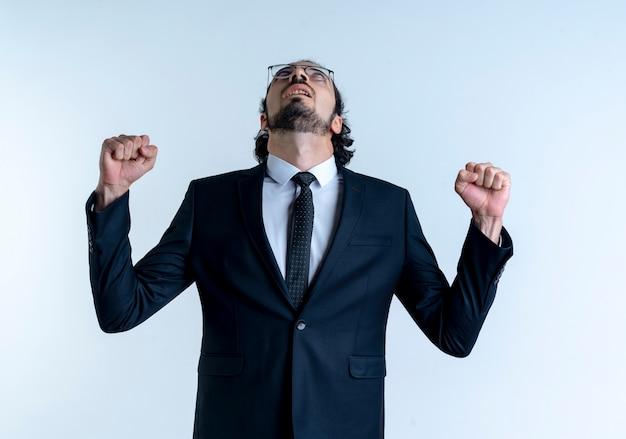 Homem de negócios de terno preto e óculos olhando para cima, os punhos cerrados, feliz e animado em pé sobre uma parede branca