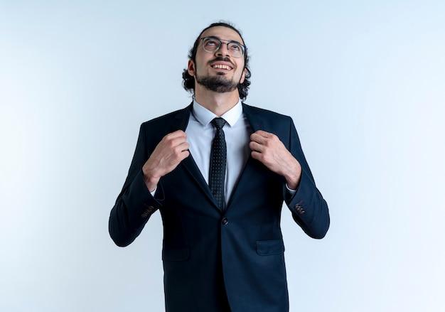 Homem de negócios de terno preto e óculos olhando para cima satisfeito consertando seu terno em pé sobre uma parede branca